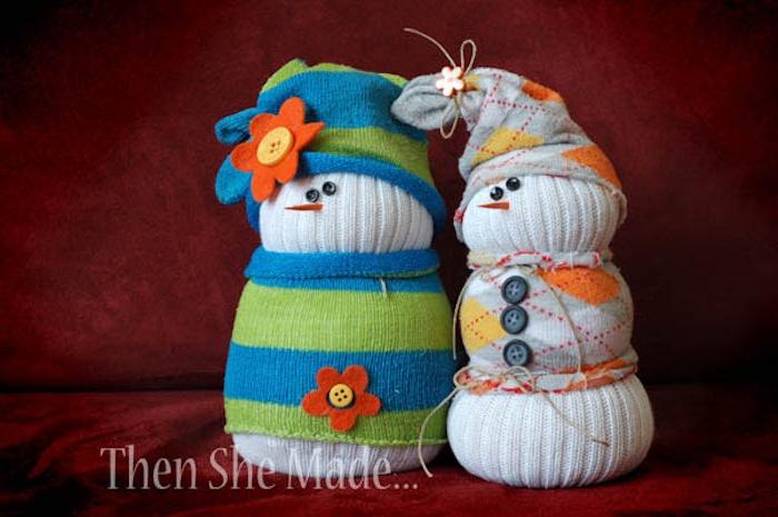 zwei weiße schneemänner aus weißen socken - mit schalen, hüten, schwarzen augen und grauen knöpfen und orangen und roten blumen
