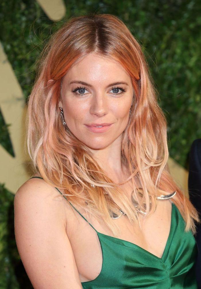 rosa haare, frau mit rosa-goldenen haaren und grünem abendkleid aus satin