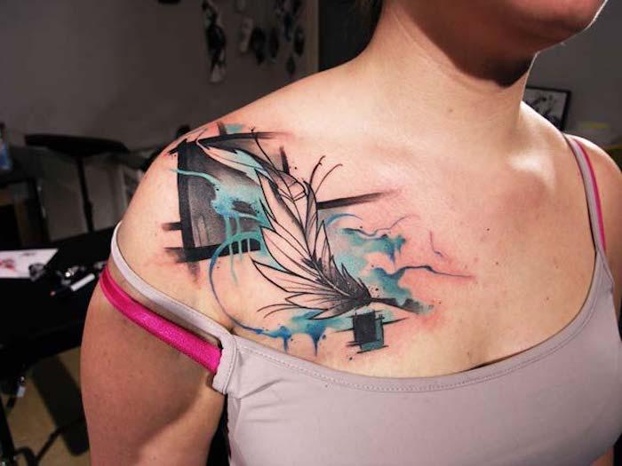 frau mit farbigem feder tattoo an der brust, tattoos für frauen