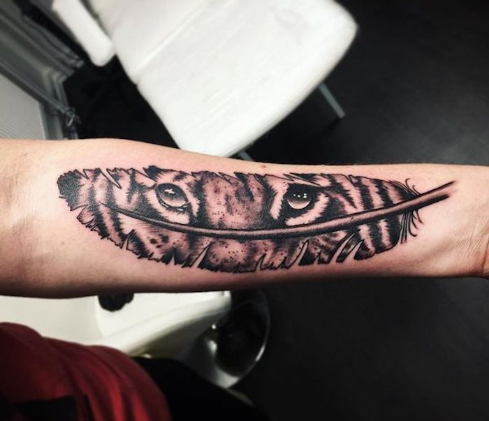 feder symbol, arm tattoo mit tigeraugen und feder, tiger tattoo