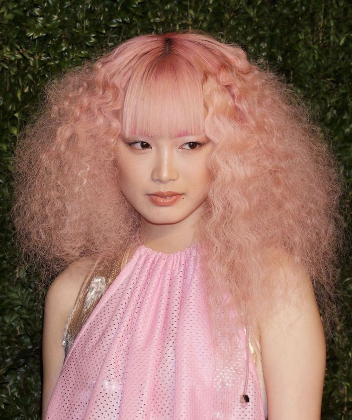 pastellfarben haare, frau mit lockgen haaren, ponyfrisur und rosa abendkleid