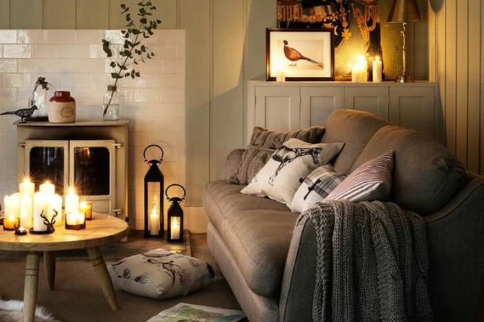 gemütliche Relaxecke mitt grauer Couch mit vielen weißen Kissen, kleiner Couchtisch aus Holz mit vielen brennenden Kerzen