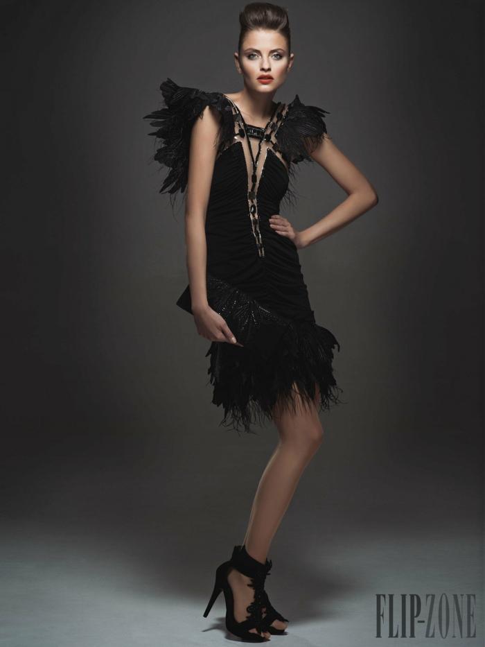 Schwarzes Cocktailkleid mit Federn und Perlen verziert, schwarze High Heels und Handtasche