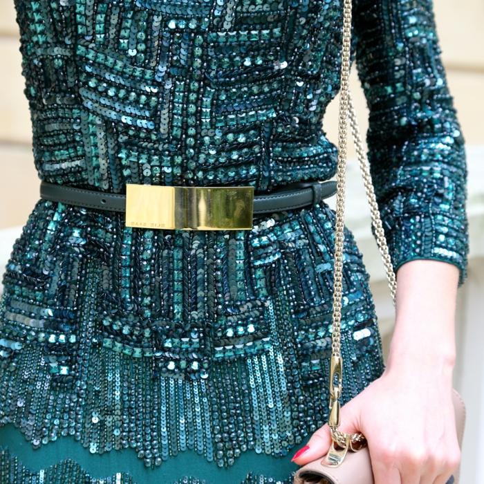 dunkelgrünes Kleid mit viellen Pailletten in unterschiedlichen Größen und Formen, schmaler dunkelgrüner Gürtel mit vergoldetem Verschluss, kleine Damentasche in Hellrosa mit einem vergoldeten Ketten-Henkel, Frau mit rot lackierten Nägel