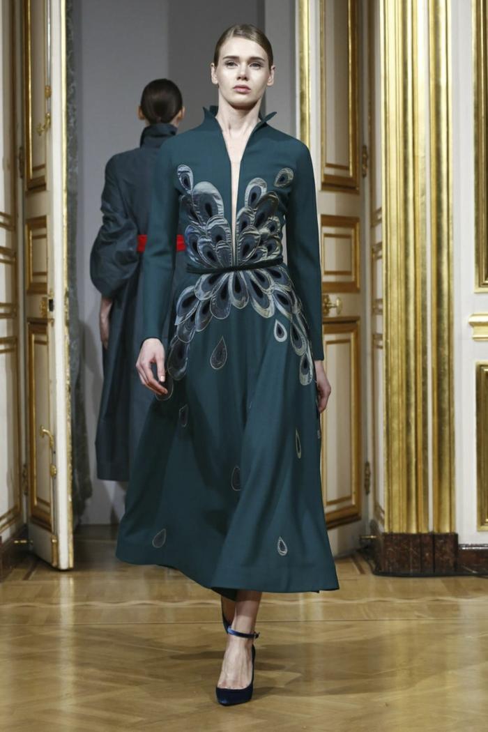 dunkelgrünes Kleid mit grau-blauem Print und einem tiefen Schlitz an der Brust, kombiniert mit einem dünnen Gürtel, der vorne schwarz ist und hinten rot