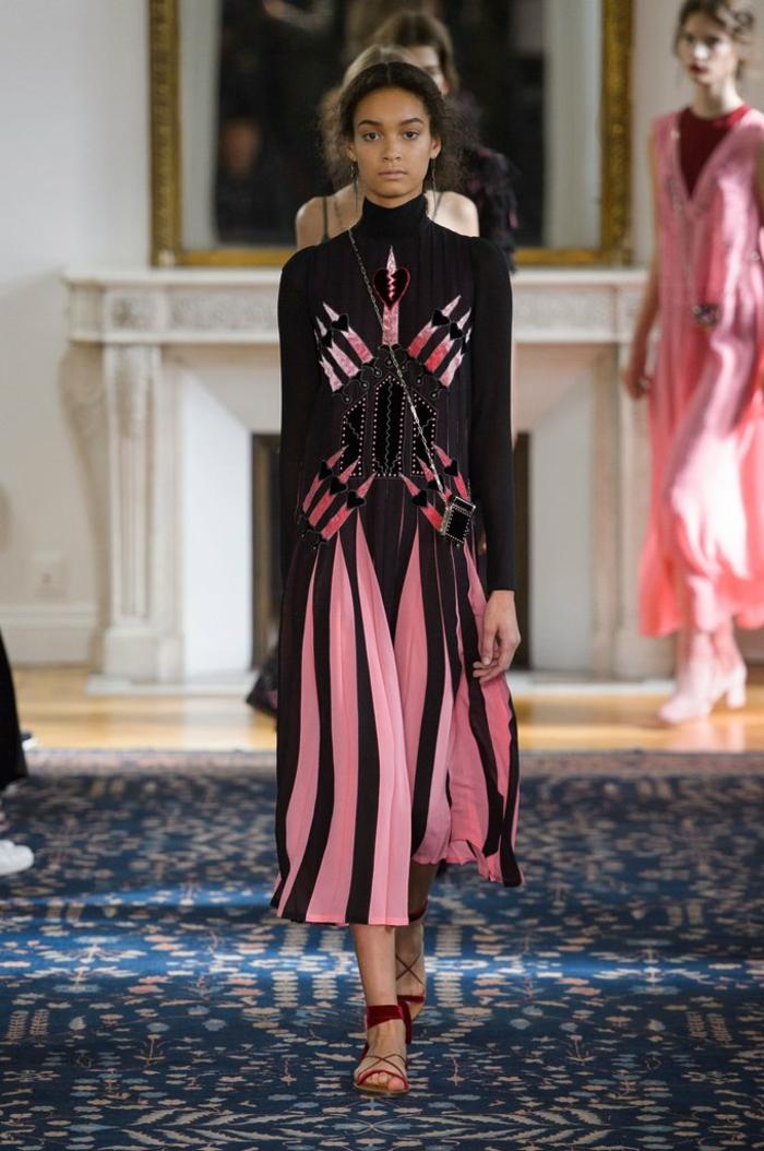 Modeschau von extravaganten Kleidern - schwarzes Pollokleid mit rosafarbenen Plissees und rosafarbenem Print, lang bis zum Fuß. getragen mit offenen roten Schuhen mit flacher Sohle