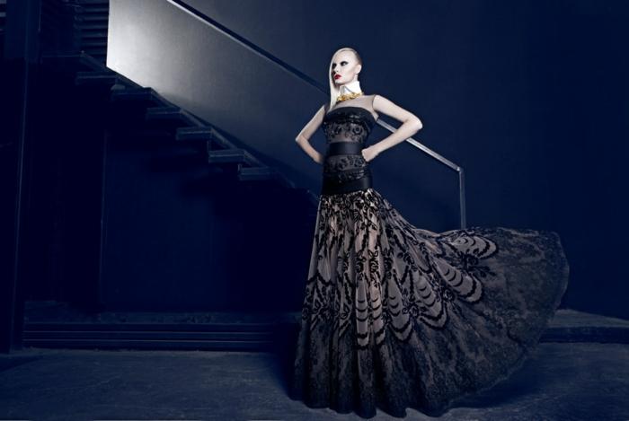langes Designer-Kleid in zwei Farben - Schwarz und Beige, gefertigt aus Seide und Spitze, schulterfreies Kleid mit drei Seidengürteln, getragen mit einem weißen Kragen, lange weißblonde Haare, starke Abendschminke, dunkles Haus mit Treppen