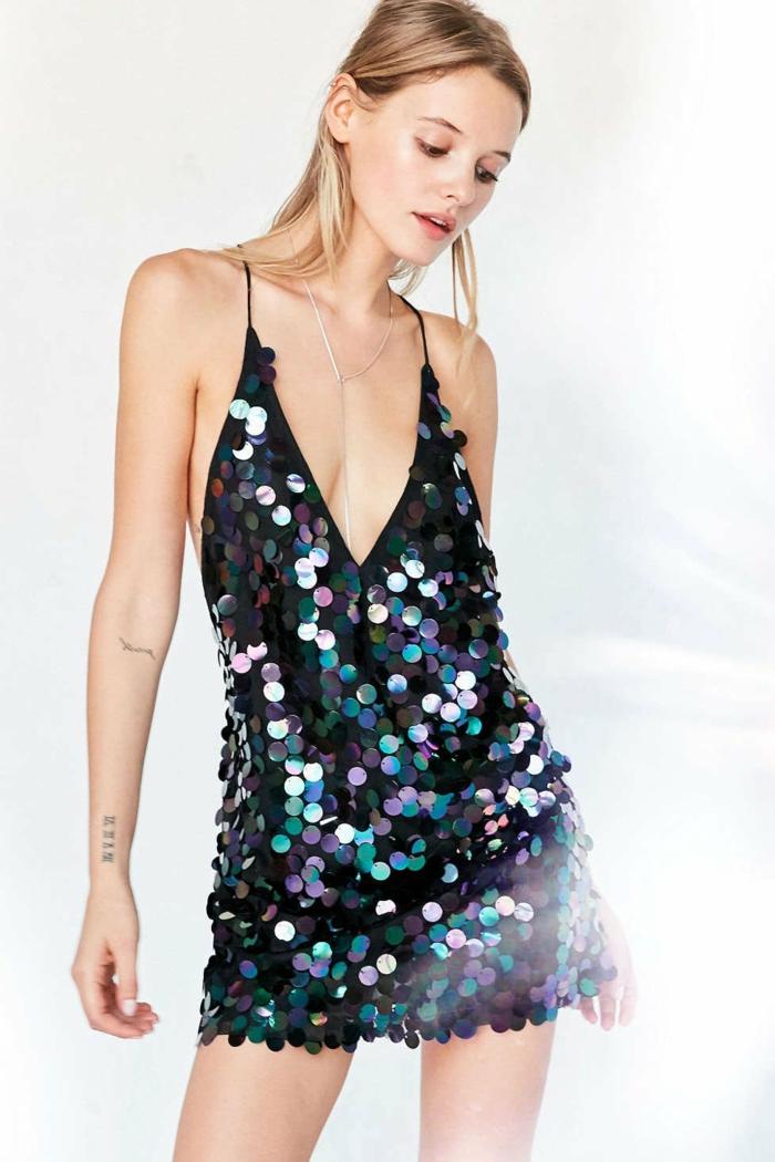 schwarzes Kleid mit Spaghetti-Trägern und einem tiefen Ausschnitt, große runde Pailletten in drei Farben, eleganter Halsschmuck aus Silber, Blondine mit Armtattoos