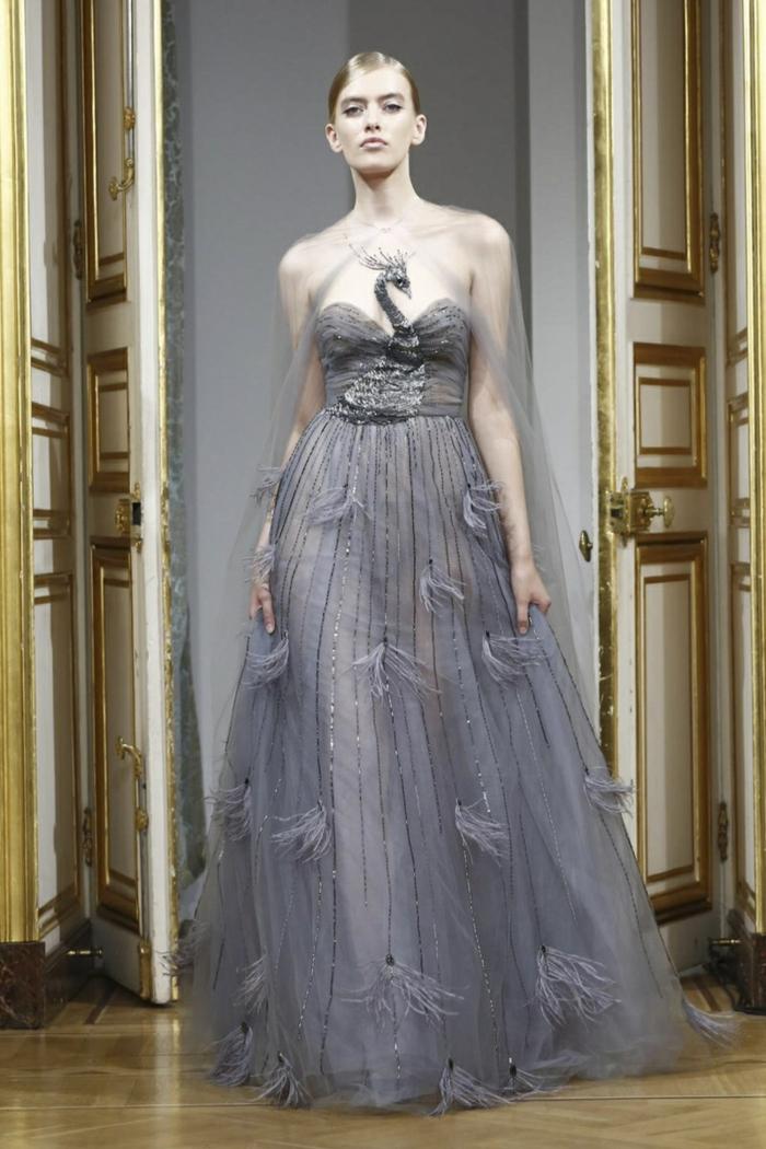 Yanina Couture-Kollektion - elegantes langes graues schulterfreies Kleid aus leichtem Stoff mit Applizierungen, Plissee-Oberteil mit Pfau-Motiv, getragen mit einem durchsichtigen Abendschal aus Tüll