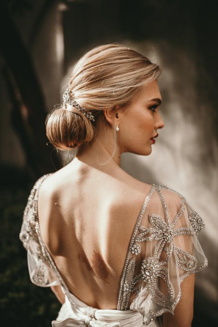 Schicke Dutt Frisur mit silbernem Haarschmuck, rückenfreies Abendkleid mit silbernen Applikationen