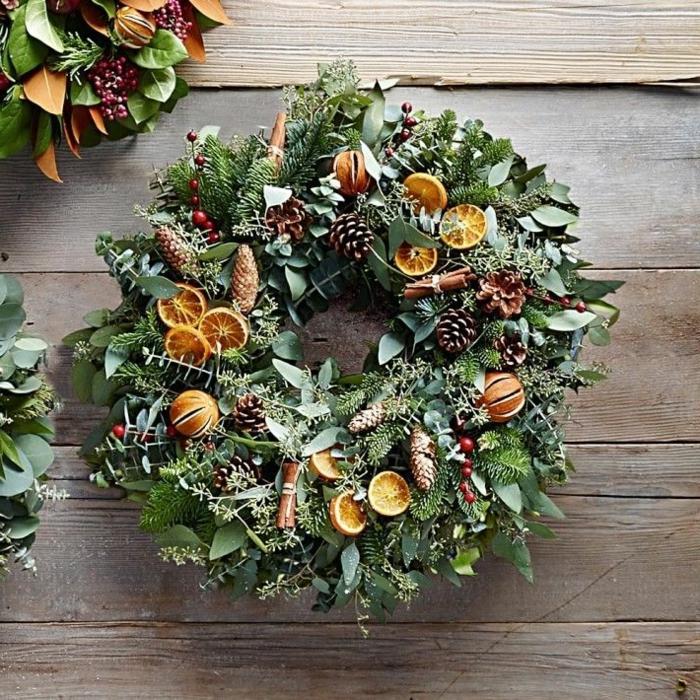 Adventskranz aus frischen grünen Zweigen aus unterschiedlichen Pflanzenarzen, getrockneten Mandarinenscheiben und Mistelfrüchten, mit kleinen Nadelbaumzapfen und Zimtstangen, Fensterbrett aus altem Holz