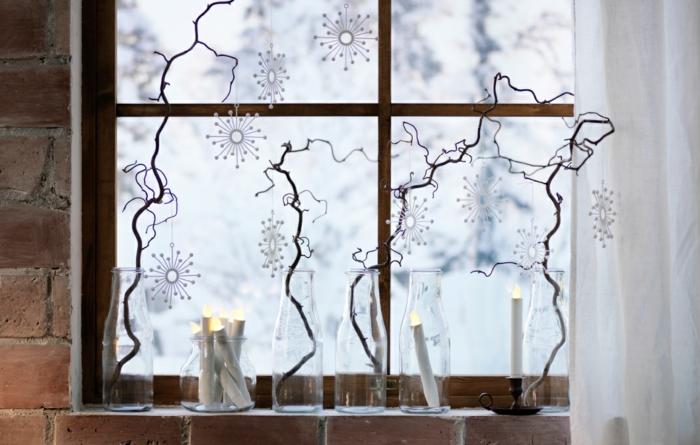 vier trockene Baumzweige, gestellt in Glasflaschen, drei Kunstkerzen in Glasvasen, Girlanden aus DIY Papier-Schneeflocken, lange weiße Gardine aus Tüllstoff, Haus mit Backsteinwand, altes Fenster mit Fensterrahmen aus Holz
