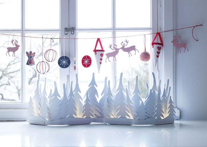 großes weißes Fensterbrett, verziert mit vielen weißen Weihnachtsbäumen aus Karton, Fenstergirlande aus Hanfseide mit verschiedenen Figuren aus Papier - weiße Konusse mit roten Henkeln und roten Herzen in unterschiedlichen Formen, Kugeln aus dünnen Papierstreifen, vier Hirschfigurchen aus Karton mit roten und weißen Punkten, weiße Schneeflocke auf schwarzem Papier, kleine bunte Engelfigur