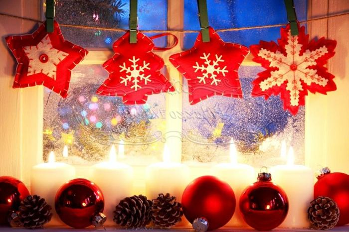 Schneeflocke aus weißer und roter Watte, verziert mit einer roten Glasperle in der Mitte, zwei Sterne in Weiß und Rot, kleiner Weihnachtsbaum aus roter Watte mit einer Schneeflocke aus weißer Watte, drei rote Christbaumkugeln mit Glanzüberzug, zwei rote Christbaumkugeln mit Mattüberzug, fünf brennende Kerzen aus weißem Kerzenwachs und vier Zapfen, rote weihnachtliche Dekoelemente, aufgehängt auf dem Fenster mit einem Bindfaden und grünen Wäscheklammern aus Holz