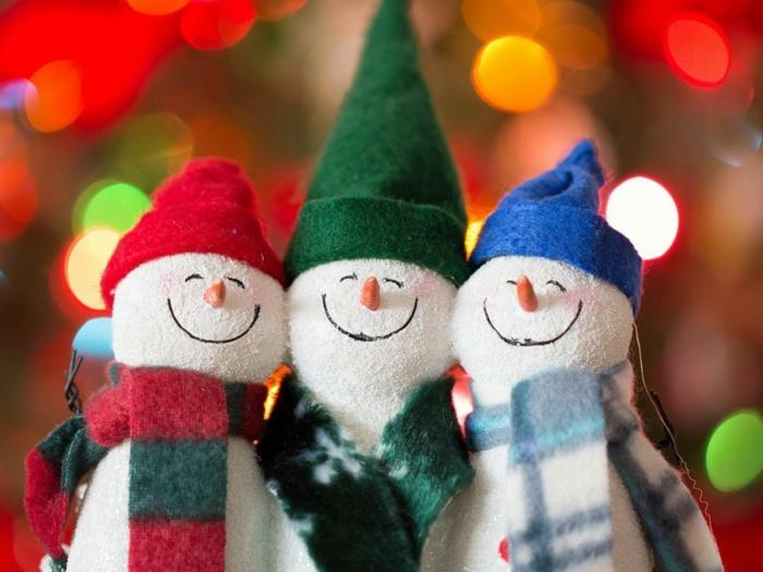 drei selbstgebastelte Weihnachtsmänner aus weißer Watte jeweils mit einem grünen, einen roten und einen blauen Hut aus Watte und mit einem Schal mit Karo- oder Schneeflocken-Muster, Weihnachtslichter in verschiedenen Farben, drei Schneemannfiguren mit orangen Nasen, geschlossen Augen und einem großen Lächeln auf dem Gesicht