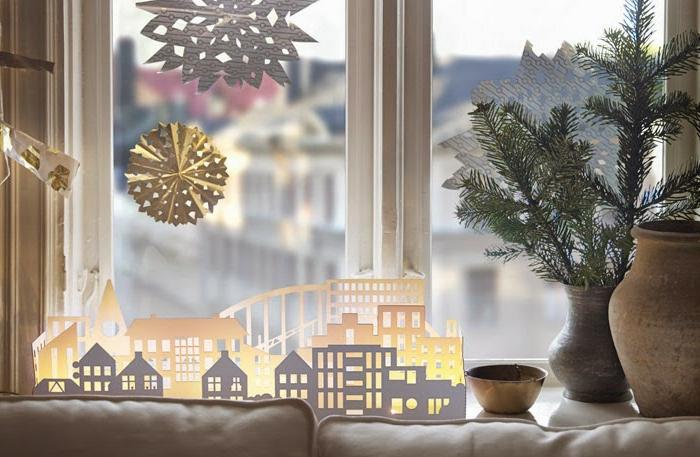 Tannenzweige in grauer Keramikvase, große Keramikvase in Beige, Stadtmodel aus weißem Papier - kleine Häuser und große Wohnblöcke, große Schneeflocken aus Papier, kleine Schüssel aus Keramik, weiße Couch mit weißen Couchkissen, Fenster mit Stadtaussicht