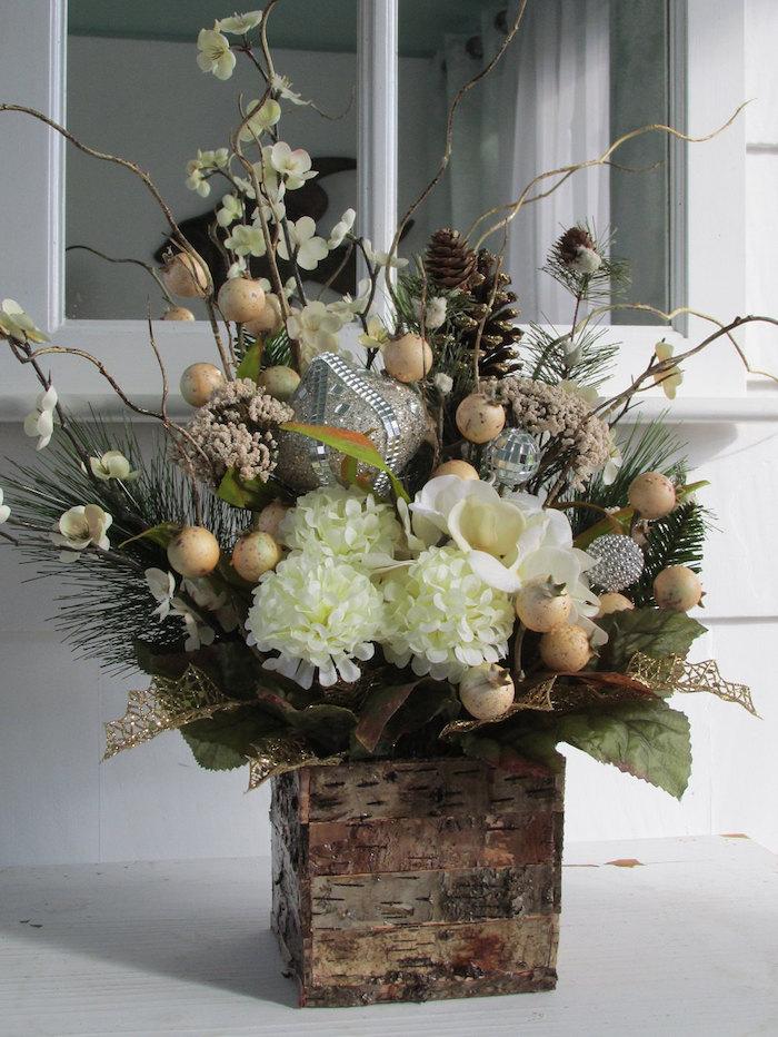 Weihnachtsgestecke eine Vase aus Holz, weiße Blume, silberne Weihnachtskugeln