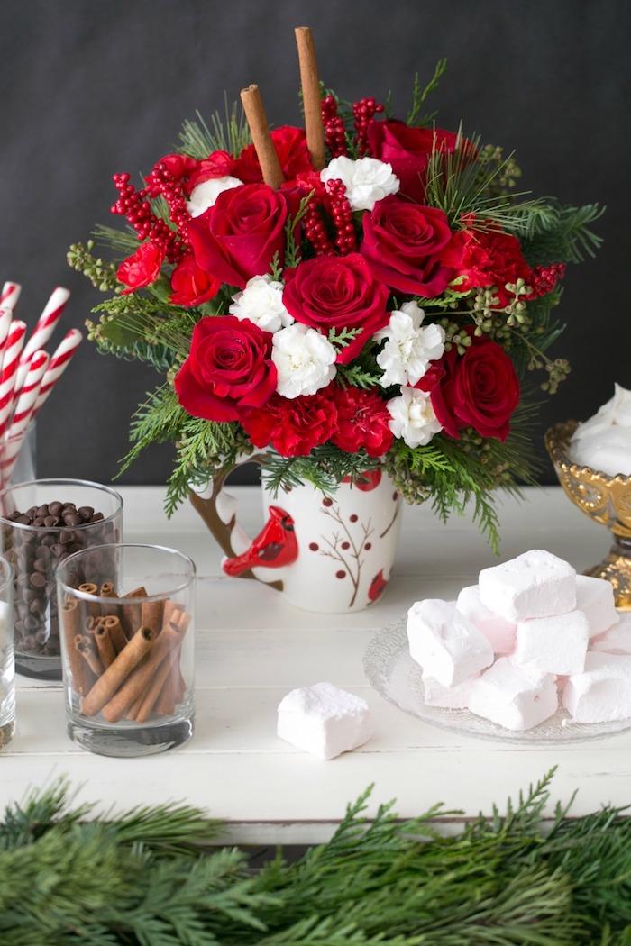 Weihnachtsgestecke - rote Rose und weiße Blumen in Kaffeebecher mit kleinen roten Vogel