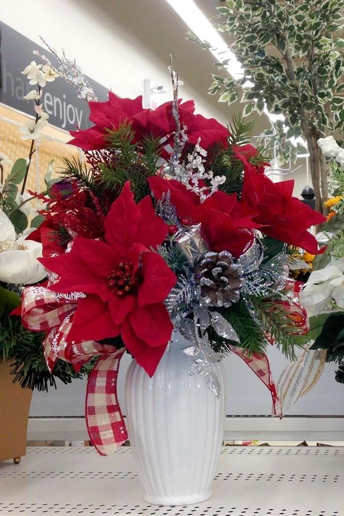 Weihnachtsgestecke aus Weihnachtssterne, Zapfen und silberne Blätter in weißer Vase