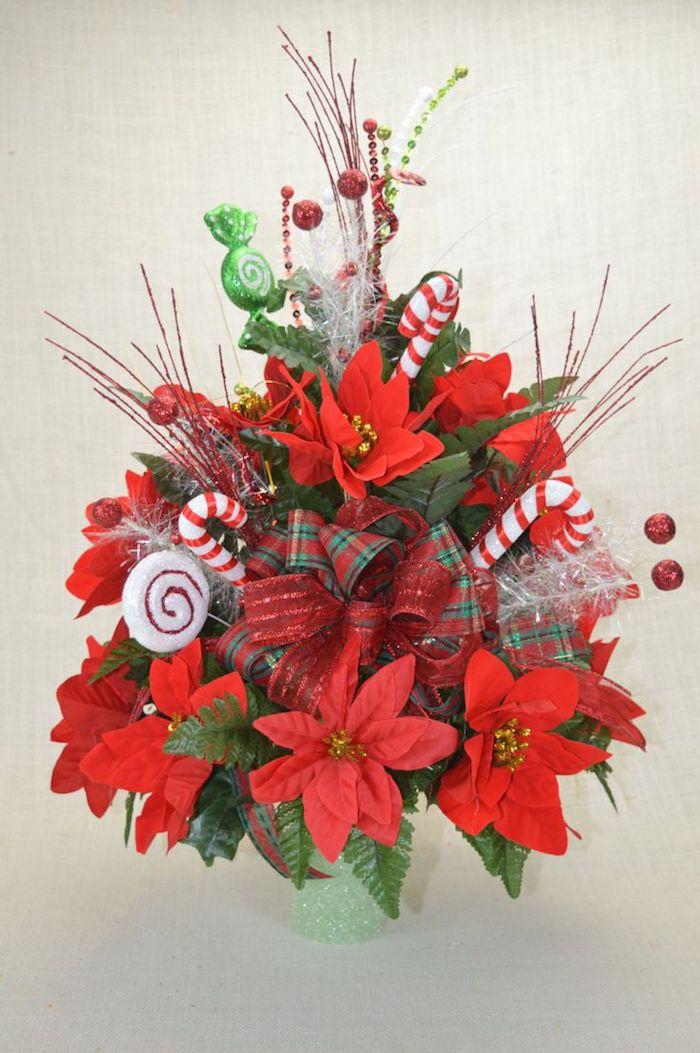 Weihnachtssterne, rote Blumen und Süßigkeiten in einer glänzenden Vase
