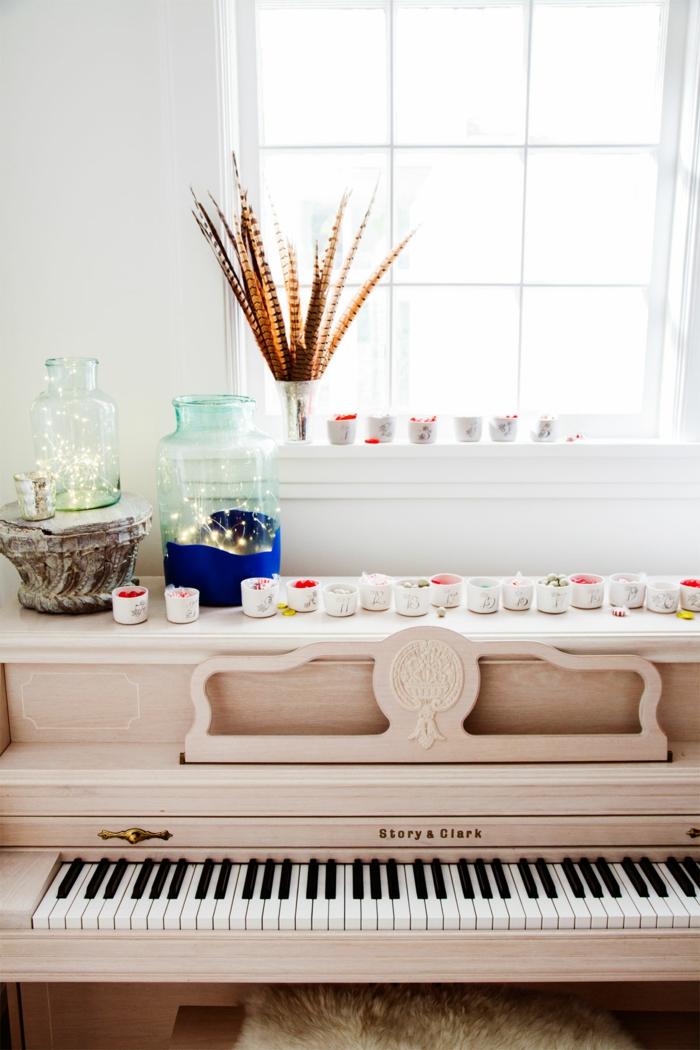 Schöne Weihnachtsdekoration, Einmachgläser voll mit Lichterketten, kleine Schalen mit Geschenken, Klavier dekorieren