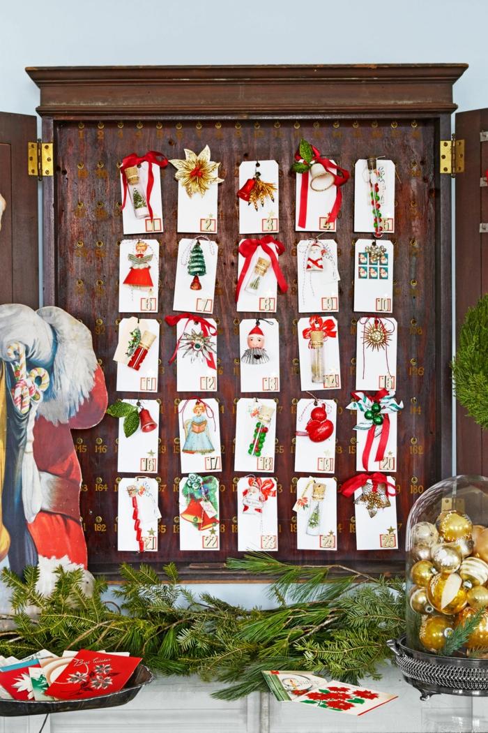 Adventskalender aus Weihnachtskarten und kleinen Geschenken, Tannenzweige und Glas voll mit Christbaumkugeln
