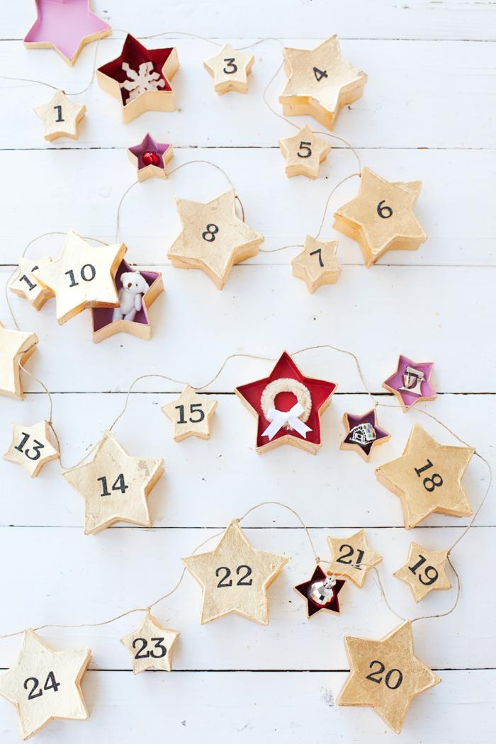 Girlande aus goldenen Sternenschachteln als Adventskalender, Schachteln voll mit kleinen Geschenken