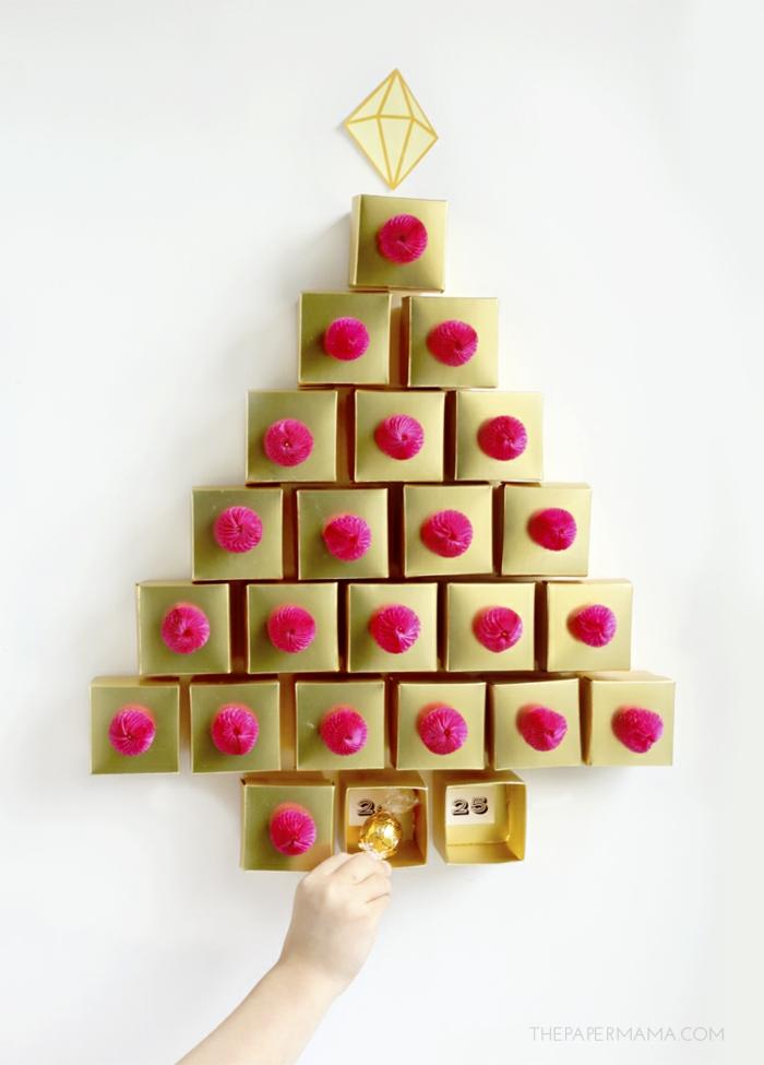 Adventskalender aus kleinen goldenen Schachteln voll mit Schokoladen Kugeln, schöner Weihnachtsbaum