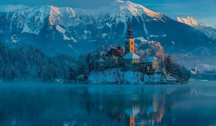 schöne winterbilder - see und eine insel mit einer kirche und kleinen häusern - winterberge mit schnee und ein wald mit bäumen und . schnee