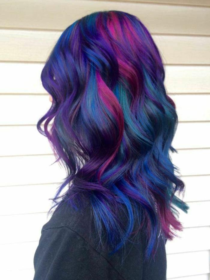 leicht gewellte bunte Haare - dunkelblaues Haar mit violetten Strähnen, blaues Haar mit grünen Reflexen, mittellange dichte Haare, Wand mit Kunststoff-Paneelen