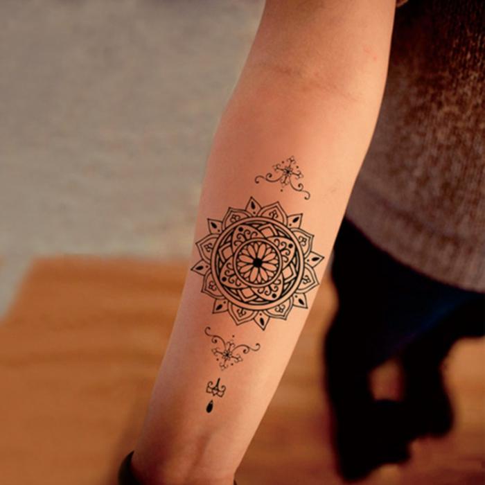 junge Frau mit Mandala Tattoo am Unterarm, kleines Tattoo amUnterarm mit Mandala-Motiven, kleine Tribal-Symbole in Schwarz