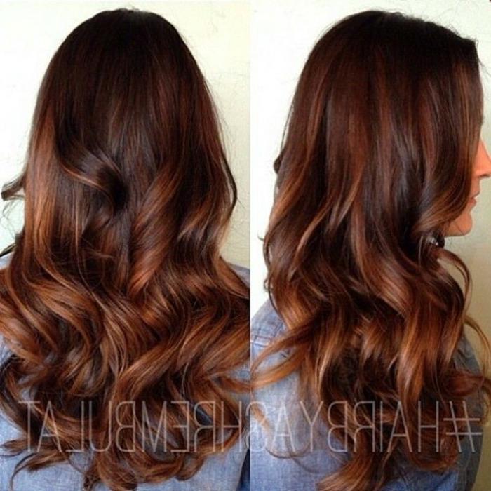 lange Haare mit dunkelbraunem Ansatz und hellbraunen Strähnen mit Locken, gefärbtes Haar mit Glanzreflexen, Frauenjacke aus Denim in blauer Farbe