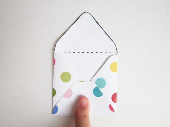 Briefumschlag basteln - einen weißen Briefumschlag mit vielen bunten Flecken