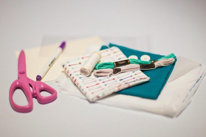 Stoff, Fäden und eine rosa Schere alles, was sie zum Umschlag Basteln brauchen