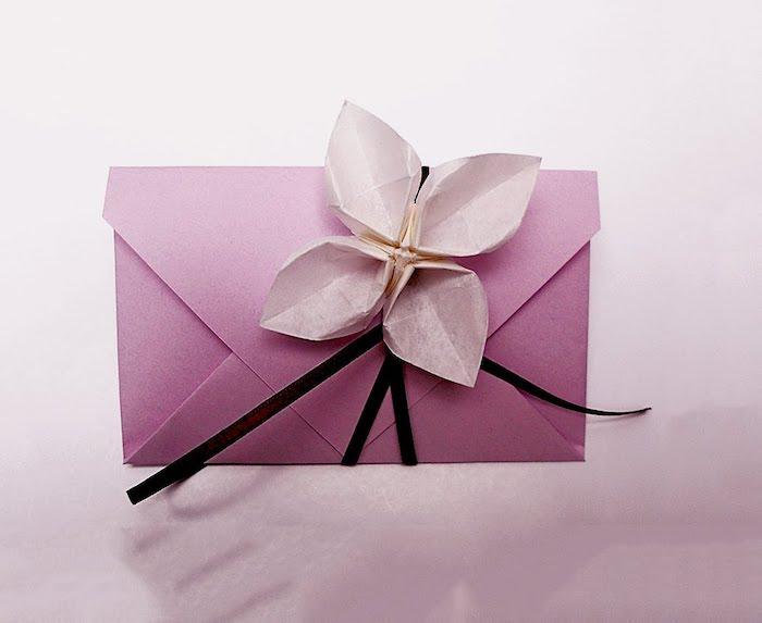 Briefumschläge basteln - eine schöne Origami Blume als Verzierung von Briefumschlag in rosa Farbe