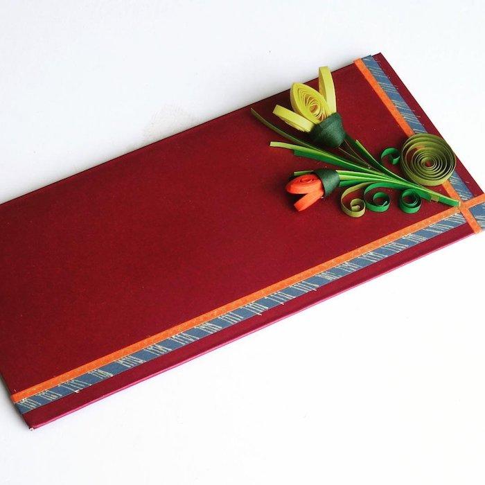 Briefumschläge basteln - ein roter Briefumschlag mit einer roten und einer gelben Papierblume