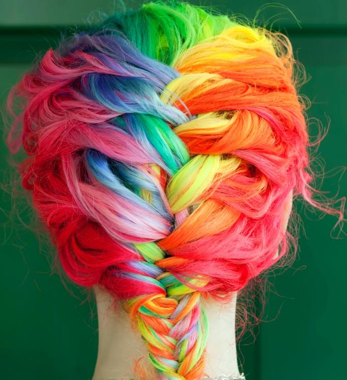 bunte Haare flechten - Regenbogen-Haare mit Fischgrätenzopf, lässige leicht gewellte Haare, Haare mit dunklem Ansatz und farbigen Strähnen, Mädchen mit dünnem Hals und weißer Haut, das vor einer grünen Wand steht