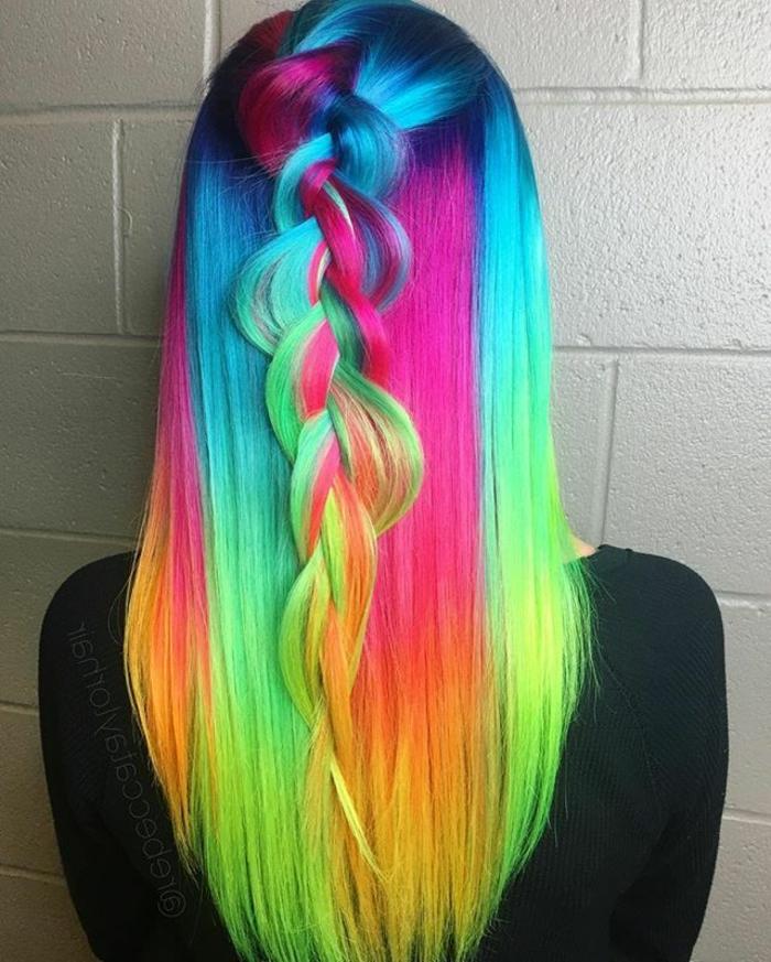 glänzende glatte Haare in grellen Regenbogenfarben, geflochten nach hinten, locker geflochtener Zopf, schwarze Damenbluse mit langen Ärmeln, hellgraue Wand mit Kunststoff-Tapeten