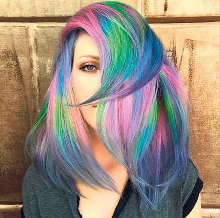 ineinander verlaufende Regenbogenfarben, grüne Augen mit Mandelform, graues T-Shirt mit schwarzem Kragen