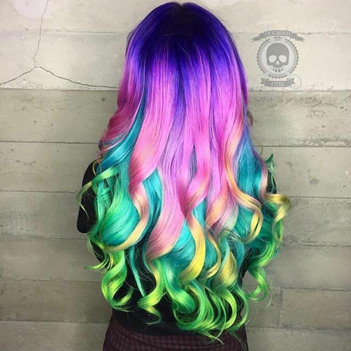regenbogen Haare mit Glanzreflexen, dunkelblauer Ansatz, Innenseite gefärbt in Türkisblau, Oberseite gefärbt in Rosa, gelbe und grüne Spitzen, große Locken an den Spitzen, Outfit - schwarze Bluse und kariertr Rock