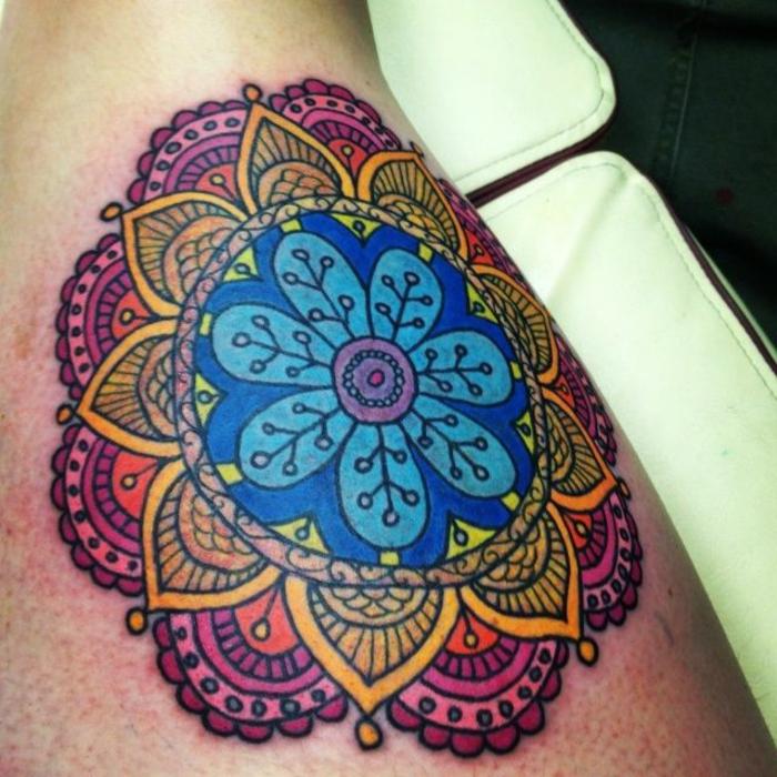 farbiger Mandala Tattoo in vier Farben - außen Violett und Orange, innen gelb und blau, Blumenmotive in vielen Farben, weiße Liege aus Leder