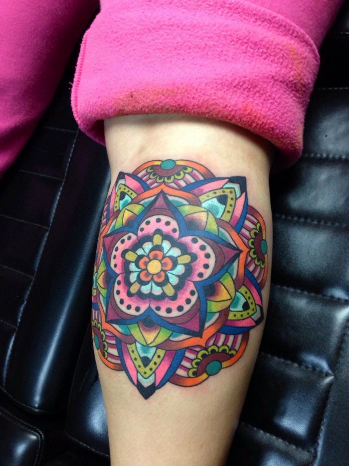 bunter Tattoo Mandala in vielen Farben und mit vielen Ornamenten, viele schwarze Punkte und Halbkreise, pinke Hose aus Plüsch, Sitz aus schwarzem Leder