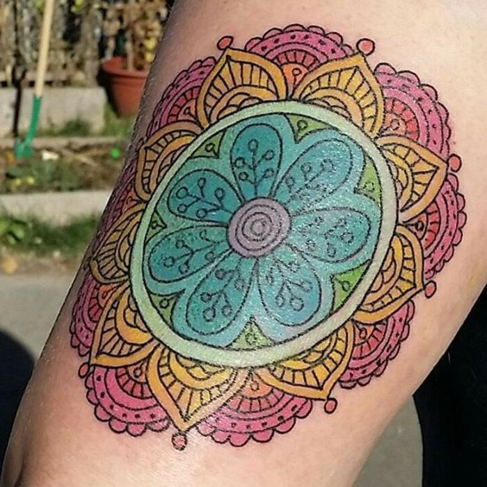 Tattoo Mandala Old School - blaue Blume mit einer Spirale in der Mitte, die Blume ist von einem türkisgrünen Kreis umkreist, dann folgen gelbe Blätter, die von lila Halbkreisen umgeben sind