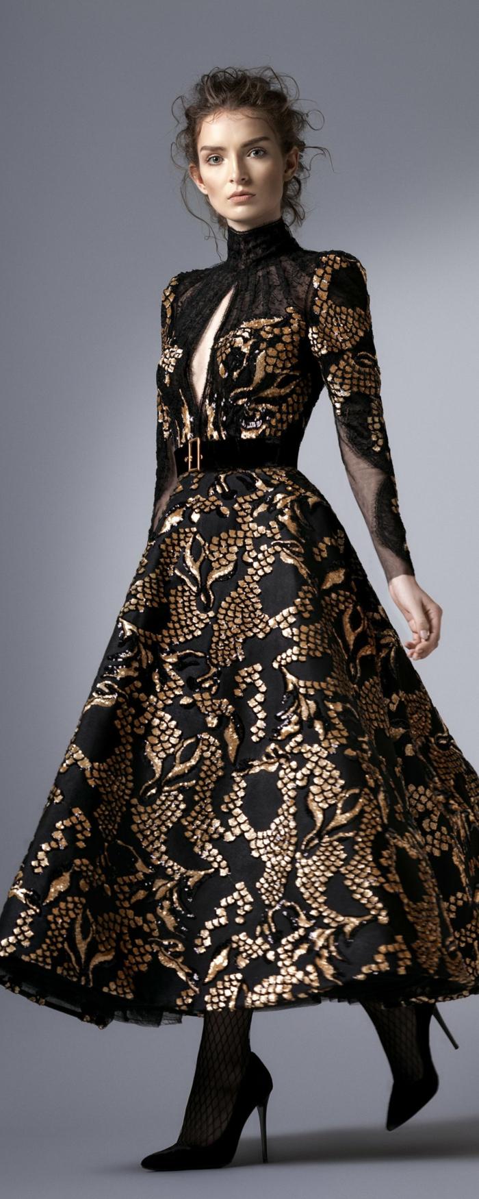 elegante Damenmode - langes Kleid in Schwarz und Goldfarbe mit einem Semtgürtel mit goldenem Verschluss, Pollokragen und offen an der Brust, lässige Hochsteckfrisur für lockiges Haar, Netzstrumpfhose und schwarze Absatzschuhe