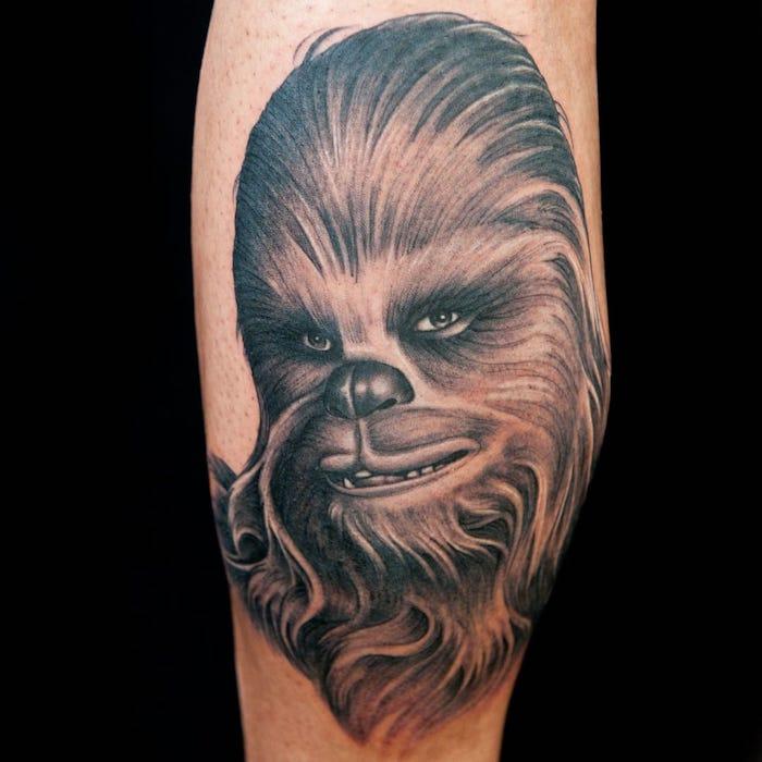 ein bein mit einem star wars tattoo mit einem großen braunen chewbacca mit einer schwarzen nase und grünen augen