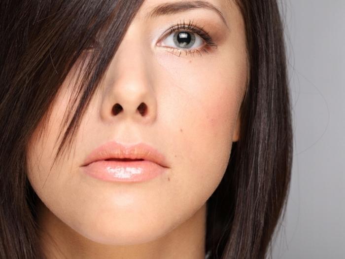 geglättete schwarze dünne Haare mit Seitenscheitel, schwarze Haare und grüne Augen, gelber Hautunterton, dicke Lippen mit rosafarbenem Lippenglanz