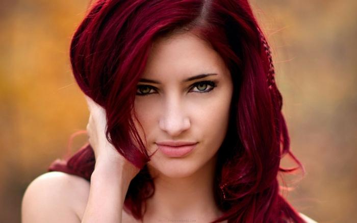 rote Haare mit Violett-Nuancen, seitlich gezogenem Scheitel, frein fallenden Strähnen und einem kleinen Zopf, grüne Augen mit kurzen Augenbraun, Mund mit dicker Unterlippe und dünner Oberlippe
