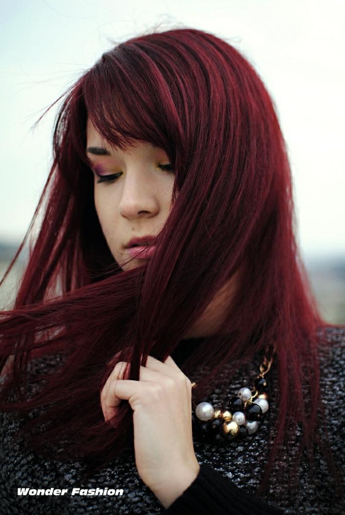 lange glatte Haare mit Seitenpony, rot gefärbte Haare mit Kirsch-Nuancen am Ansatz und duneklen Mahagoni-Nuancen auf den Längen, grauer Stickpulli und eine Perlenkette mit großen weißen und schwarzen Perlen, Mädchen mit halbgeschlossenen Augen, geschmikt mit Kirsch-Augenschatten
