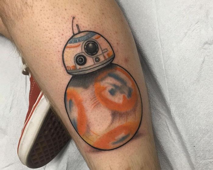 beine mit roten schuhen und mit einem tattoo mit einem orangen kleinen star wars roboter