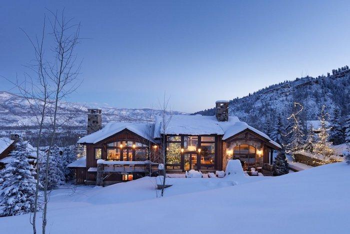 schönes winterbild mit einem blauen himmel und einem wald mit bäumen mit schnee und einem haus